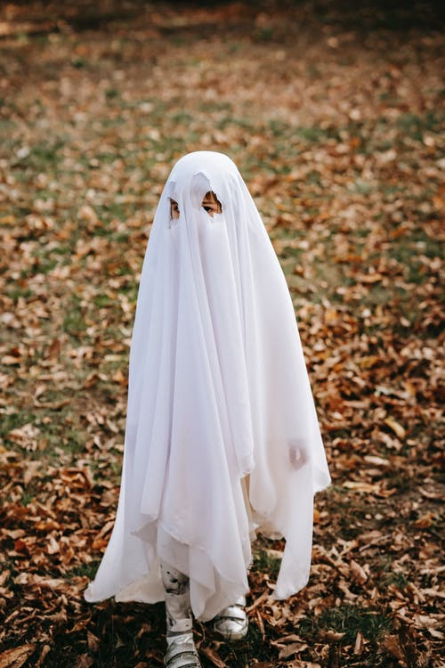 From above full body of anonymous child wearing white ghost costume standing on grassy ground with fallen leaves during Halloween celebration against blurred background