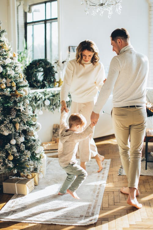 Family Dancing Beside a Christmas Tree