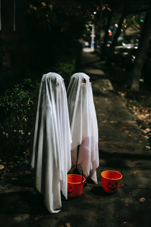 Full body side view of anonymous kids wearing white ghost costumes standing on sidewalk with orange buckets while playing trick or treat in evening