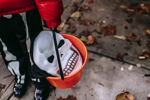 Person in Red and Black Jacket Holding Orange Plastic Bucket With Black and White Plastic Spoon