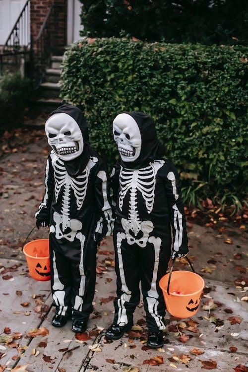 Person in Black and White Skeleton Costume Standing Beside Orange Plastic Bucket