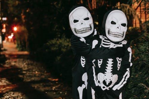 Unrecognizable children in skeleton costumes hugging on street