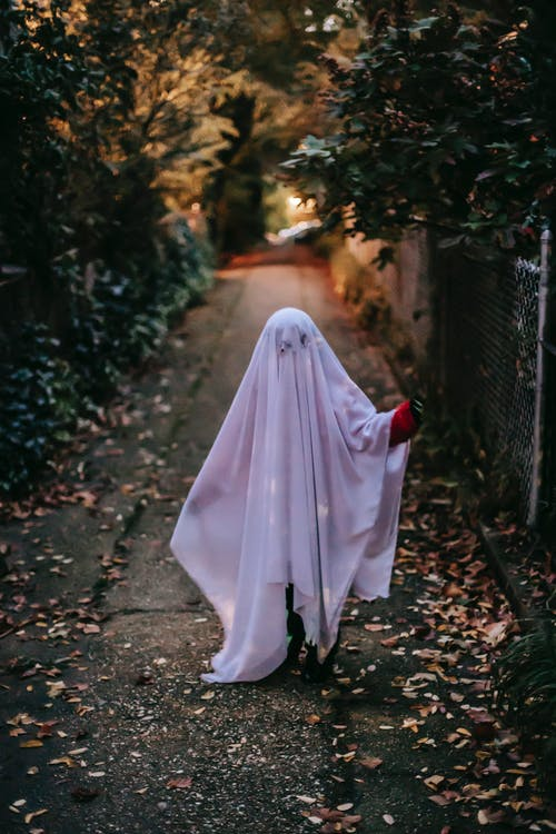 Full body of anonymous child wearing ghost costume strolling on narrow pathway along trees on street in evening against blurred background during Halloween celebration