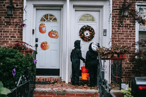 Anonymous kids in skeleton costumes playing trick or treat