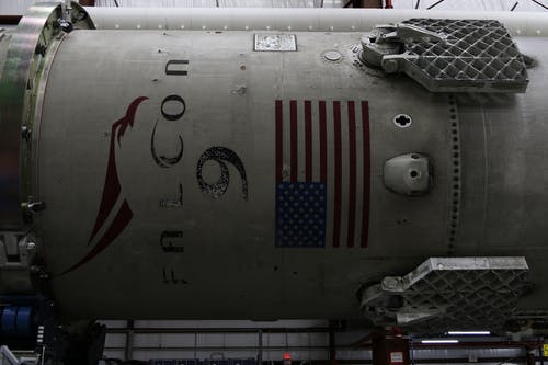 Fragment of modern spacecraft with printed flag of United States of America during assembly in rocket factory