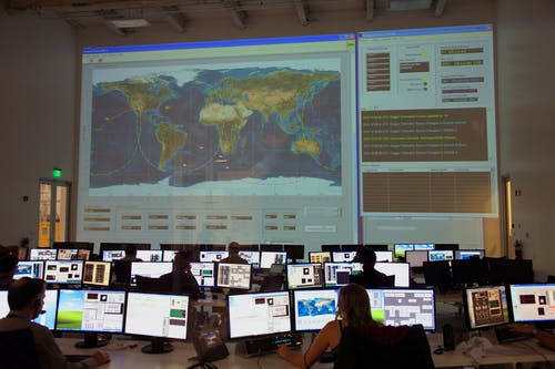 Group of colleagues working in modern office with big map on screen