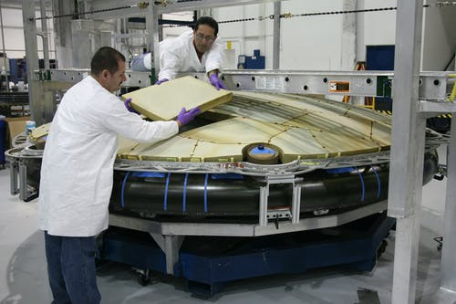 Professional mechanics installing spaceship detail at factory