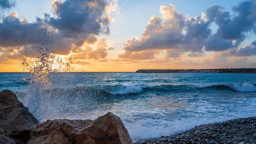Breathtaking scenery of stormy ocean with foamy waves crashing on rocky formation and washing pebbled coast under amazing cloudy sunset sky