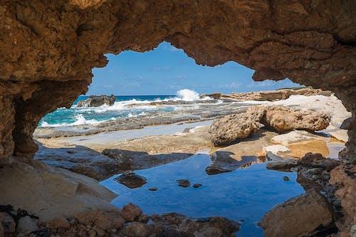 Rocky coast of wavy sea under blue sky