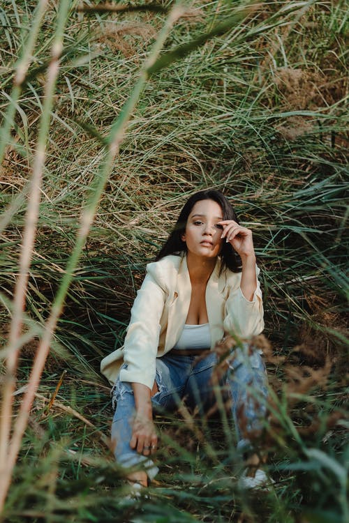 Woman in White Long Sleeve Shirt and Blue Denim Jeans Sitting on Brown Grass