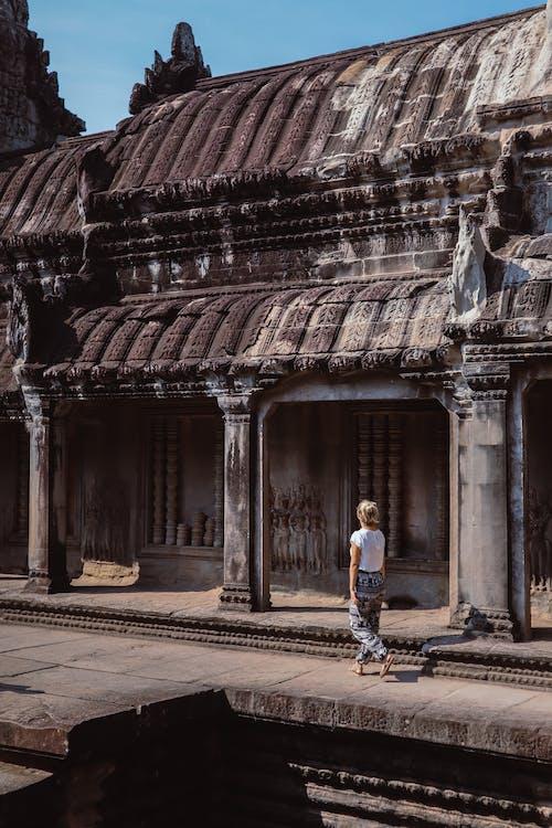 Man in Blue Shirt and Black Pants Walking on Sidewalk