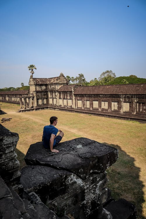 Man in Blue T-shirt Sitting on Rock