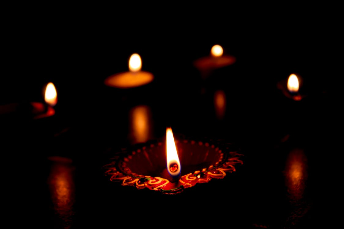 Lighted Candle on Black Surface