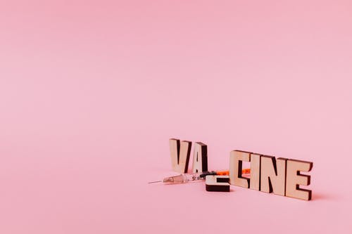 A Syringe and Vaccine Text on Pink Background