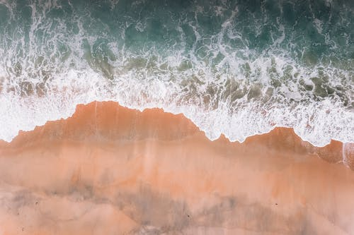 Drone view of waves with foam of deep blue ocean running against sandy coast in soft daylight