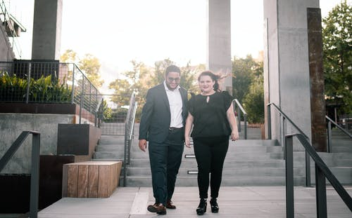 Full length of positive young man and woman smiling while walking downstairs together during date in city park
