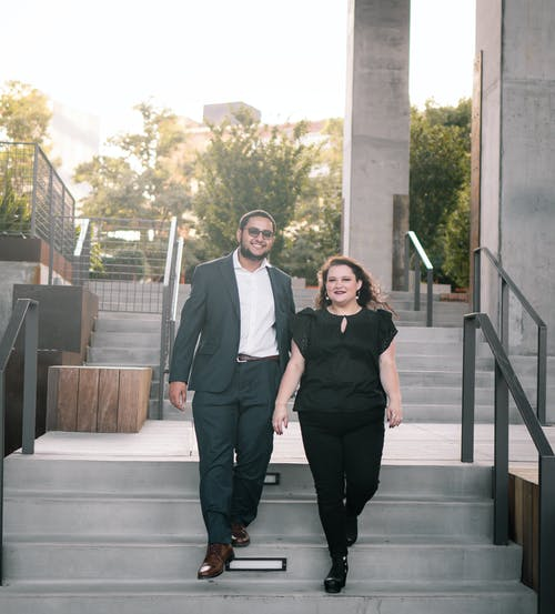 Full body of cheerful young elegant man and woman smiling and walking downstairs  during romantic date in city park