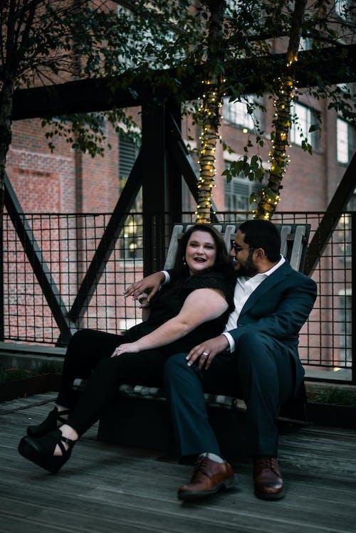 Stylish young couple cuddling while sitting on bench on veranda
