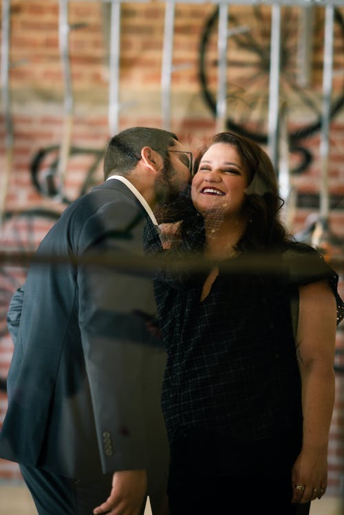 Young elegant bearded man in suit kissing cheek of happy smiling girlfriend during romantic date in city