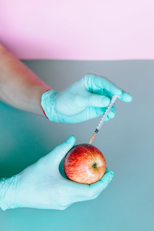Person Injecting a Red Apple by Using a Syringe