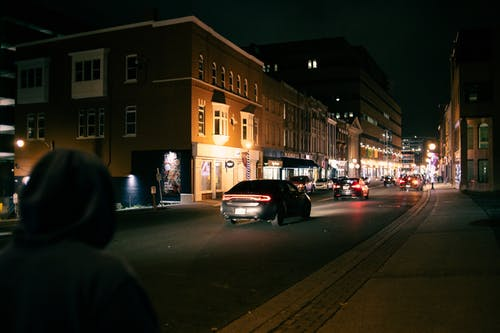 Back view of unrecognizable person in hood strolling along asphalt road with moving vehicles with glowing headlights at night