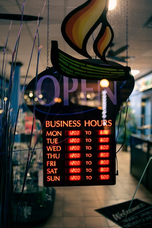 Through glass of information board with glowing business hours hanging on glass door at entrance of cafe