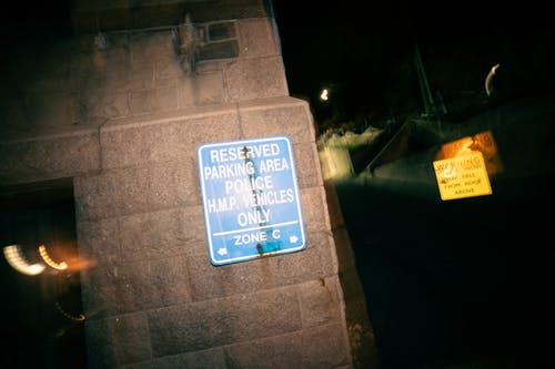 Signboard restricting parking for cars on reserved area for police vehicles at night