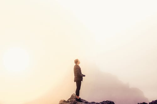 Man in Black Jacket Standing on Rock Formation Holding a Camera on a Foggy Day