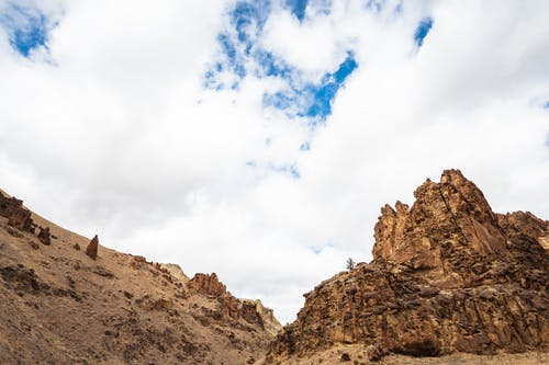 From below of rough stony terrain with uneven rocks on dry land of desert in daytime
