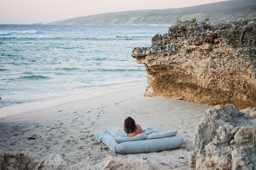 Woman Lying on a Bed on the Beach Looking at the Sea