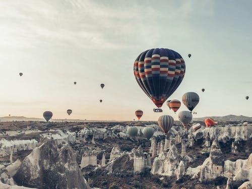 Multicolored hot air balloons flying above famous vast rocky valley in Cappadocia Turkey on early morning on fair weather