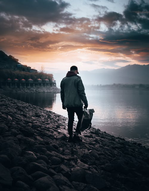 Man in Gray Jacket Standing on Rocky Shore during Sunset