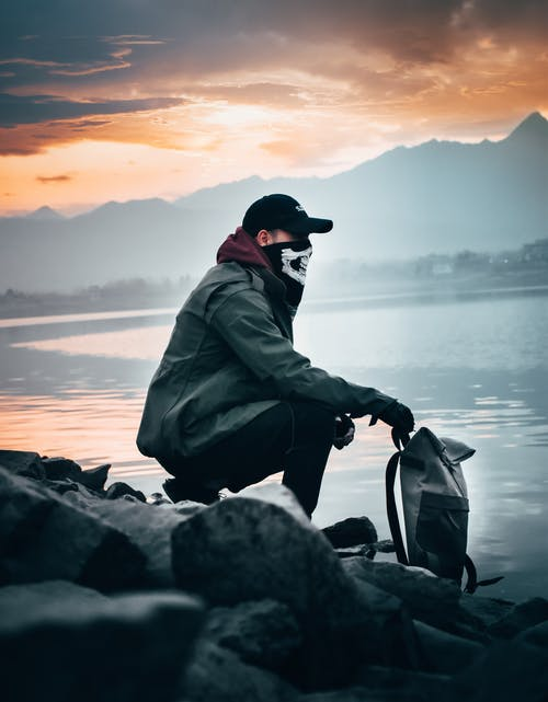 Man in Green Jacket and Black Cap Sitting on Rock Near Sea