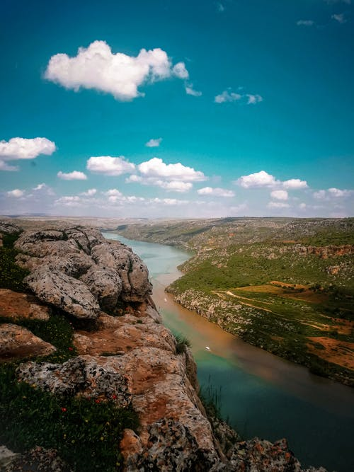 Breathtaking scenery of spacious green terrain with rocky formations and calm blue river flowing beneath clear blue sky