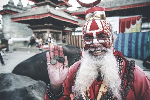 Cheerful Nepalese man in authentic costume demonstrating coins on palm
