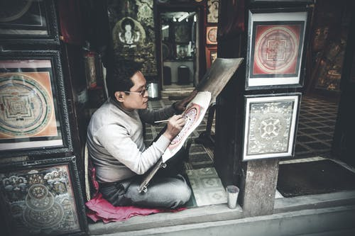 Side view full length focused Asian male artist in casual clothes drawing traditional paintings in authentic art studio