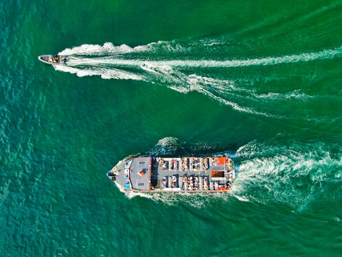 Aerial View of White and Brown Boat on Sea
