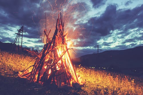 Burning bonfire with sparks in darkness