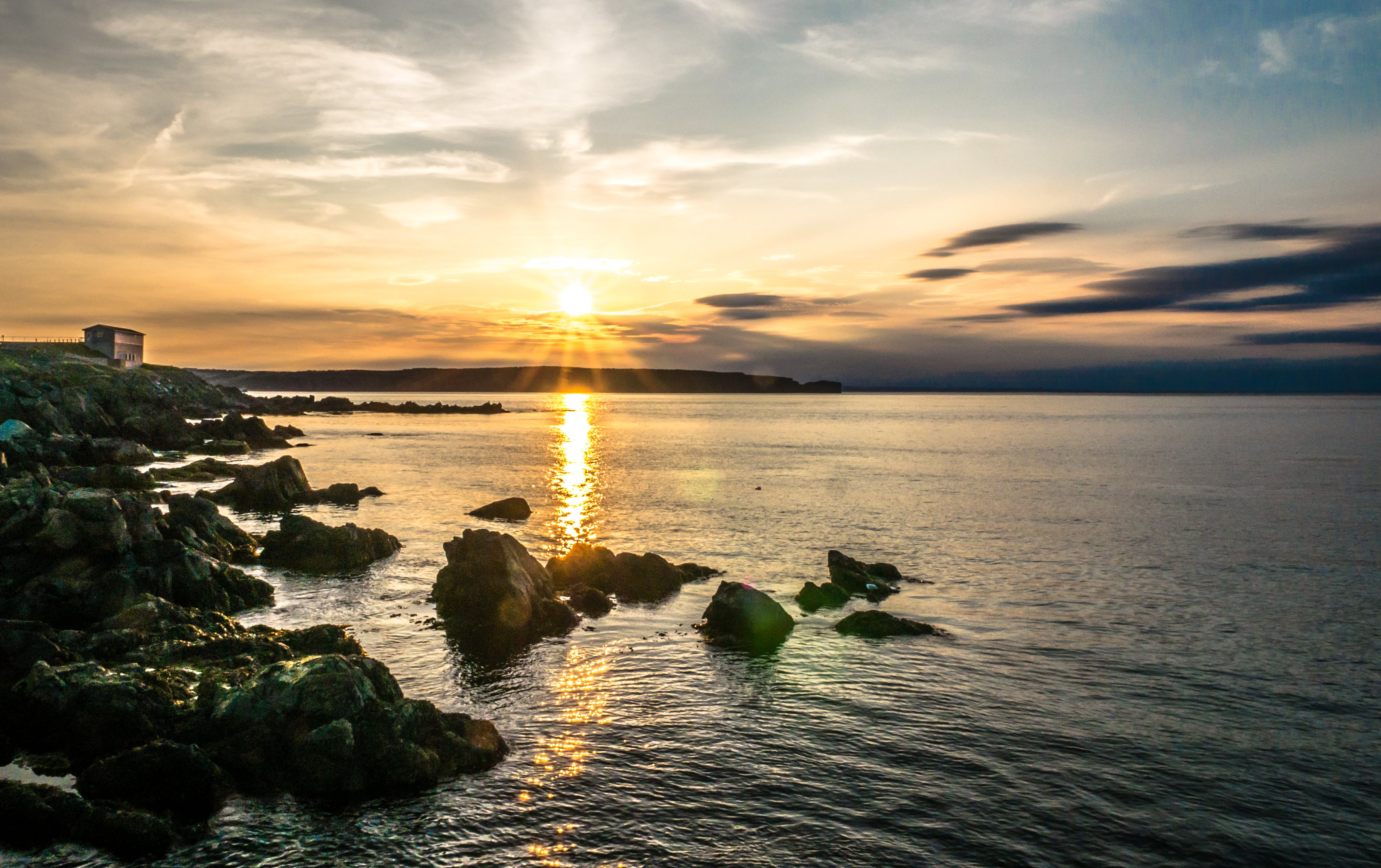 Rock Formations Beside Body of Water during Golden Hour