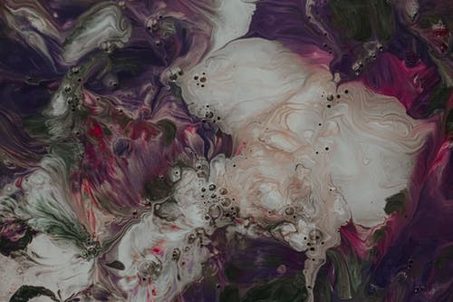 Abstract background representing stains of spilled paint of different dark colors and white pearl paint with little bubbles while making fluid art