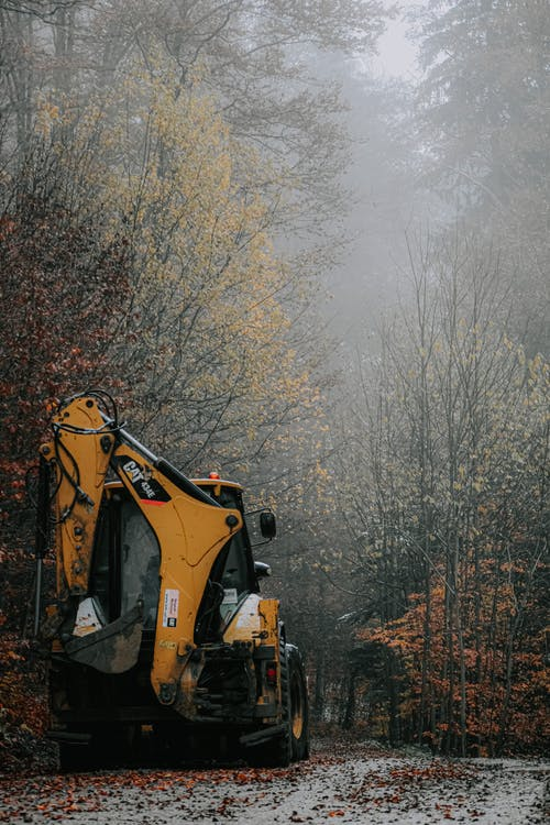 Digger on road near forest in autumn