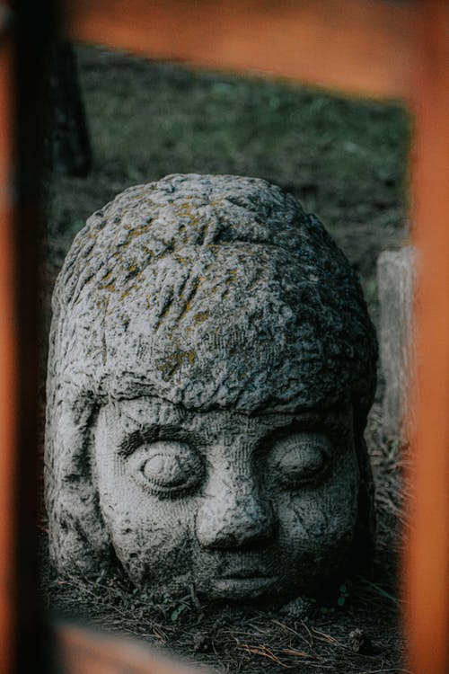 Through fence view of ancient gray stone head in helmet sculpture with big eyes buried on ground with old grass by chin