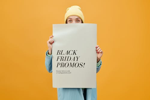 Woman in Blue Long Sleeve Shirt Holding White Poster