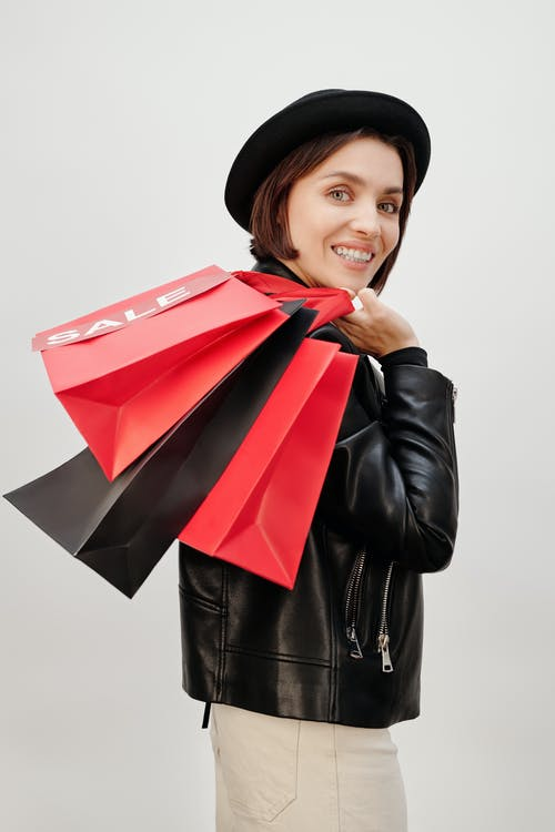 Woman in Black Leather Jacket Holding Shopping Paper Bags