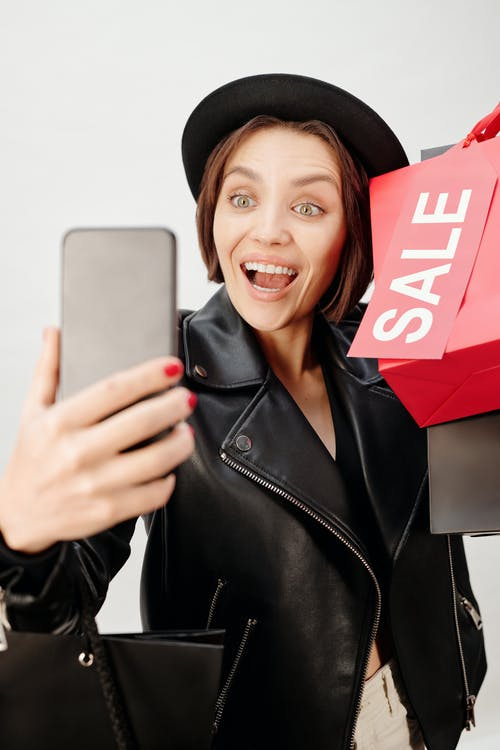 Smiling Woman in Black Leather Jacket Holding Shopping Bags