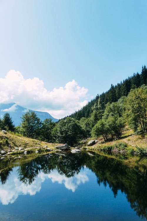 Picturesque view of river reflecting green trees growing on mounts under blue sky with clouds in summer