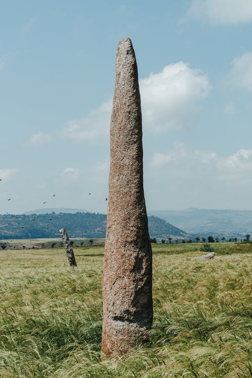 High megalith on grass meadow with mounts behind