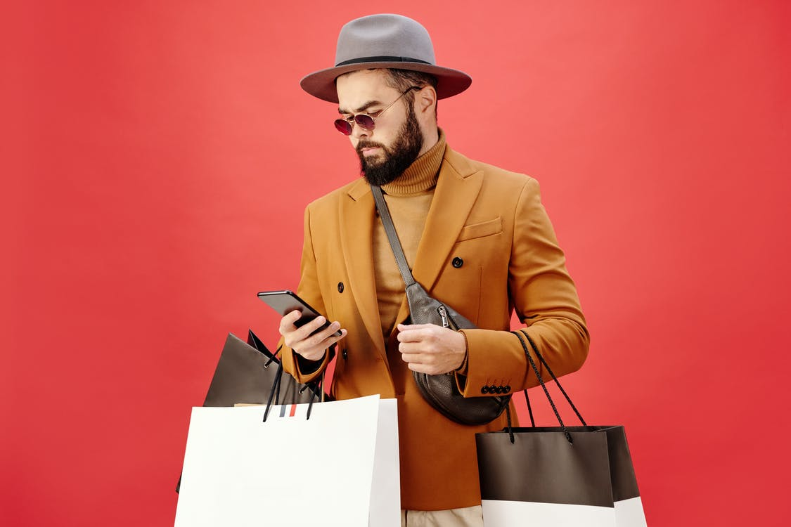 Man in a Brown Blazer Carrying Shopping Bags while Using His Cell Phone