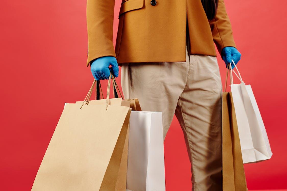 Hombre En Camisa De Manga Larga Marrón Y Pantalón Gris Con Bolsa De Papel Blanco