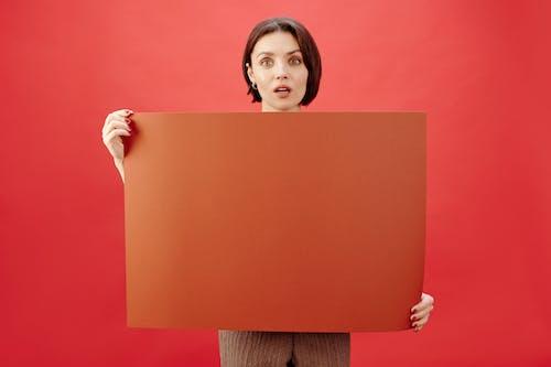 Mujer Sosteniendo Papel Marrón Con Fondo Rojo.